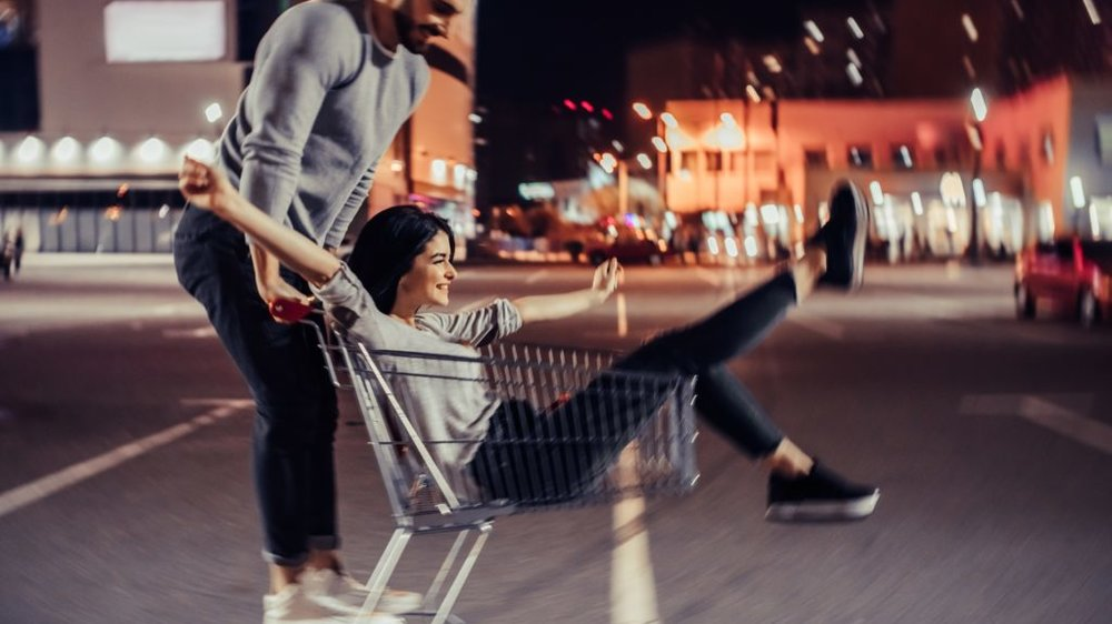 Young romantic couple is having fun with supermarket cart in the evening. Handsome bearded man and attractive young woman are spending time together outdoors.
