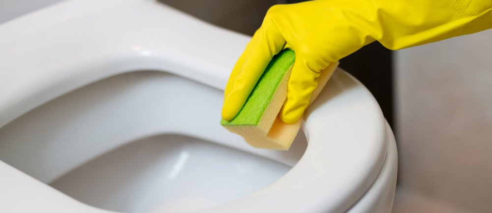 Female hands with yellow rubber gloves cleaning toilet in wc with yellow sponge. Spring cleaning
