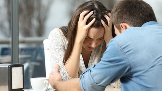 Male comforting to a sad depressed female who needs help in a coffee shop. Break up or best friend concept