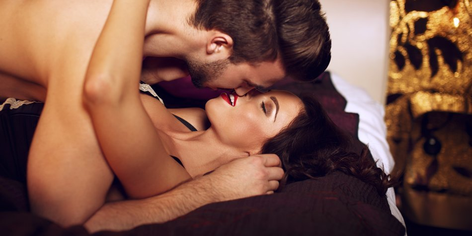 Sexy woman kissing with young macho lover on bed