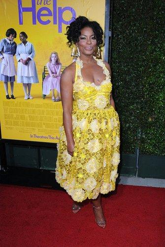 The Mentalist-Darstellerin Aunjanue Ellis in einem gelben Kleid.