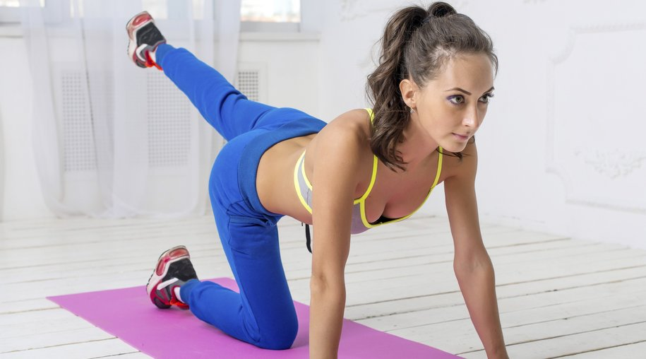 Young dark-haired athletic sporty slim woman with ponytail workout leg swing doing yoga in the gym.