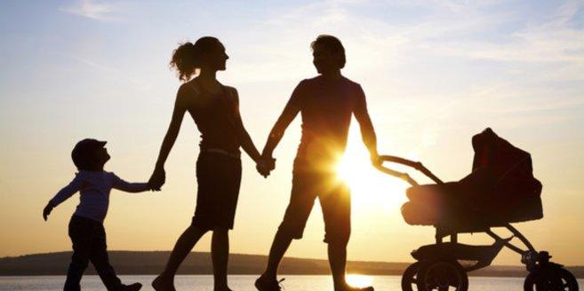 Elternzeit: Eltern gehen mit ihren zwei Kindern spazieren.
