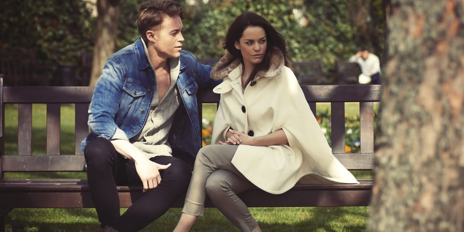 Portrait of young Caucasian heterosexual couple in fashionable clothing sat on a sunny London park bench