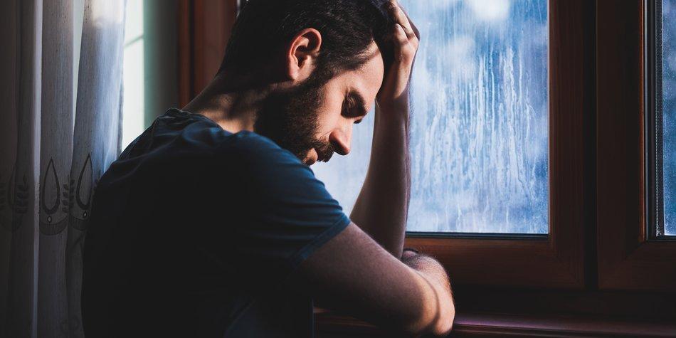 Junger Mann steht traurig am Fenster