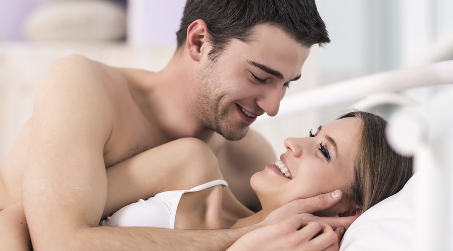 Beautiful young loving couple lying in bed