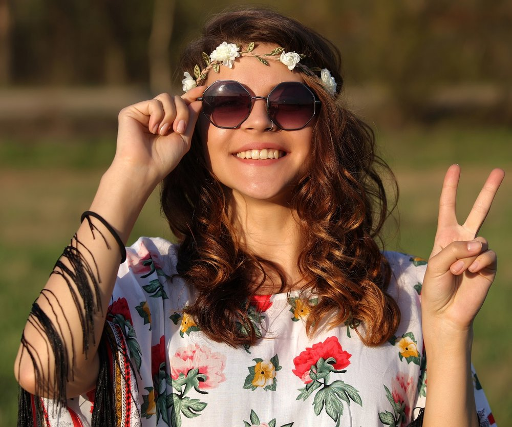 Happy young girl hippie smiles and showing sign of peace