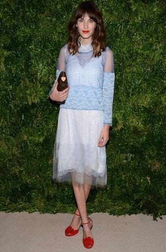 Alexa Chung mit hellblauer Bluse und weißem Rock