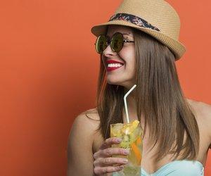 Pretty stylish girl in bikini holding cold drink