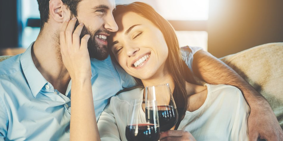 Beautiful young loving couple sitting close to each other and drinking red wine