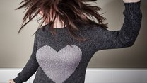 Girl wearing a sweater with heart jumping on the bed