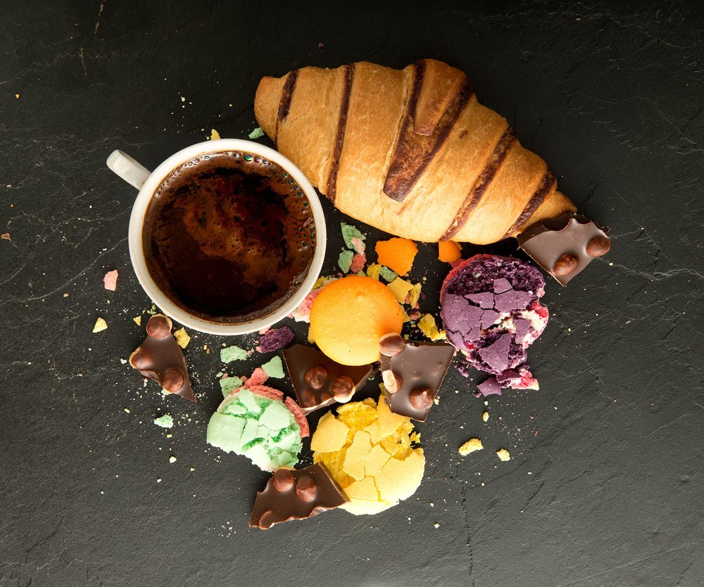 Cup of coffee with macarons and croissant on black stone table