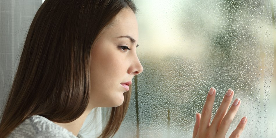 Sad woman looking the rain falling through a window at home or hotel