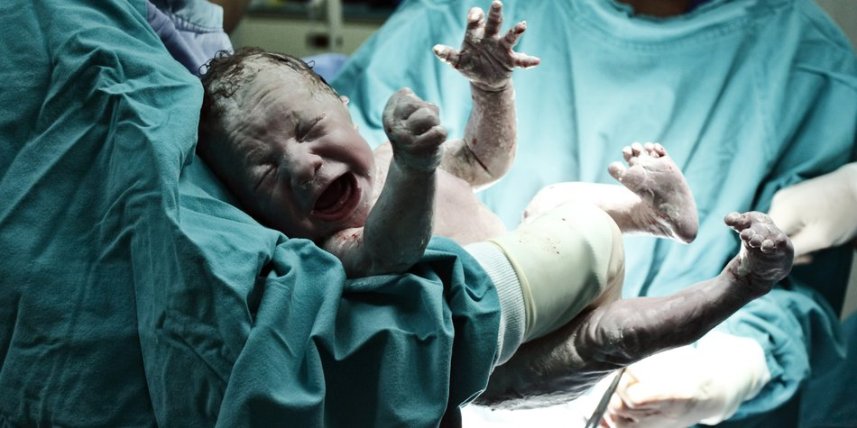 A doctor holding a beautiful baby boy minutes after the birth.