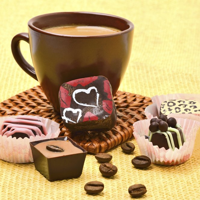 Cup of coffee with chocolate sweets and coffee beans on the tablecloth