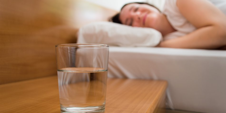 woman lying on bed with closeup of glass of mineral water on the nightstand
