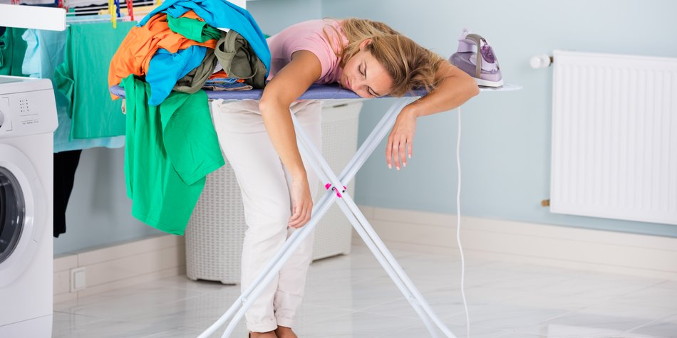 Young Tired Woman Sleeping On Ironing Board Next To Pile Of Clothes At Home